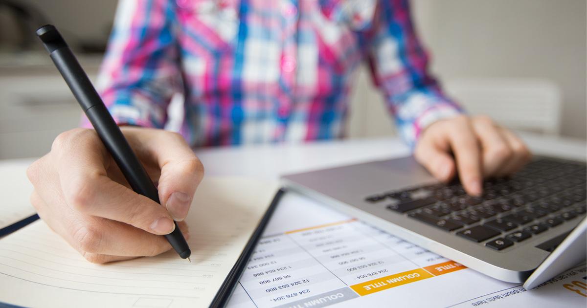pessoa olhando computador e escrevendo algo em um papel